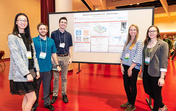 Students standing with a poster presentation