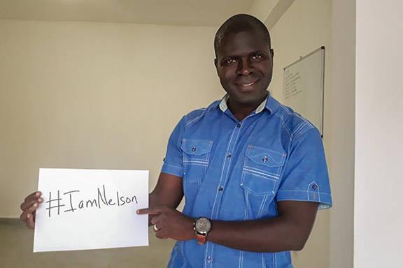 Alumnus holding an #IAmNelson sign