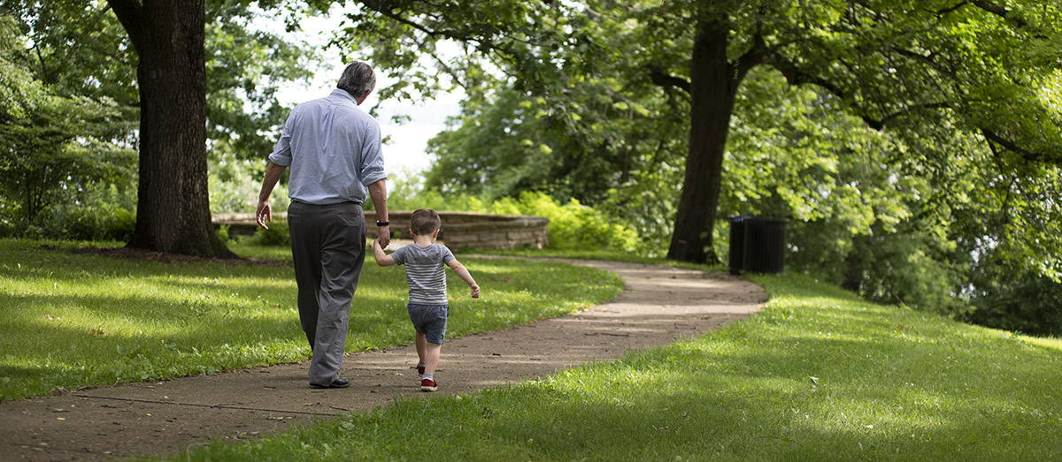 Paul Robbins and his son walking on a path in a park